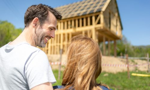 Couple looking at their new house under construction, planning future and dreaming