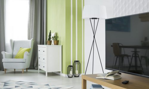 Green and white living room with tv, dresser and armchair